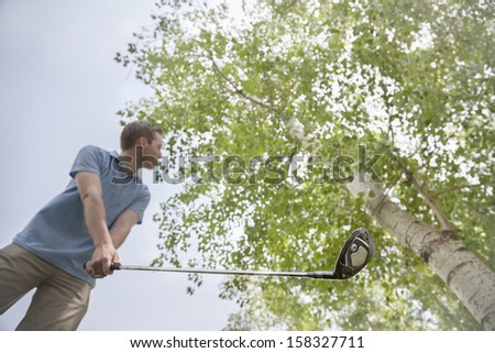 Low angle view of young man hitting golf ball on the golf course - stock photo