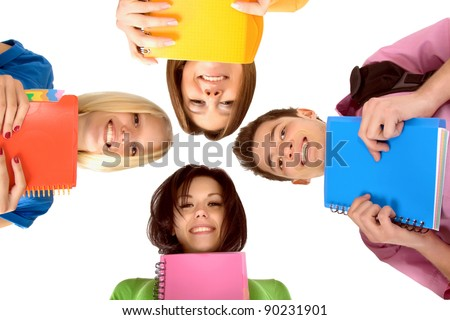 Low angle view of young people happy smile standing in circle looking down at camera, four students with books, notepad, isolated over white background - stock photo
