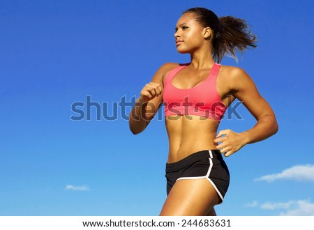 Low angle view of young woman in sportswear jogging against blue sky - stock photo