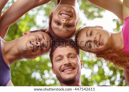 Low angle view on group of four smiling male and female friends with heads together looking downward with trees in background