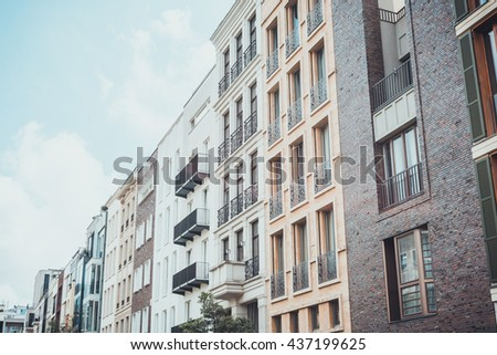 Low angle view on row of upscale residential apartment condominium exteriors under hazy partly cloudy skies - stock photo