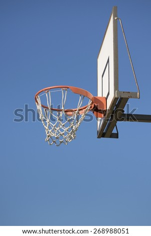 Low angle view outdoor basketball basket against clean blue sky. - stock photo