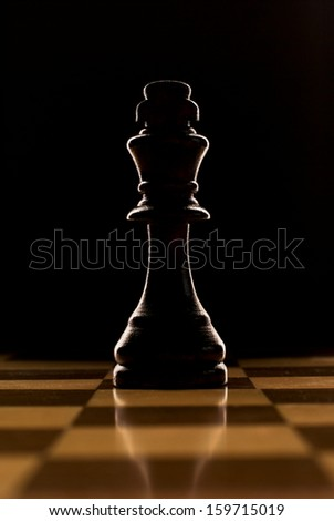 Low angle view over a reflective chessboard of a backlit chess piece - the king - against a dark background - stock photo