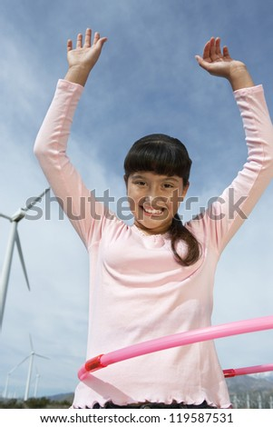 Low angle view portrait of a teenage girl dancing with hula hoop - stock photo