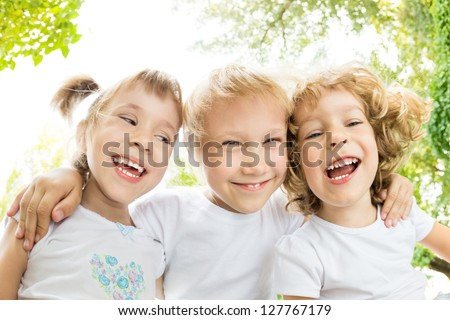Low angle view portrait of happy children laughing outdoors in spring park - stock photo