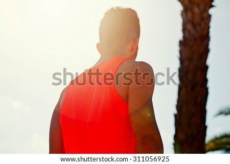 Low back view of young male jogger in bright orange t-shirt enjoying the sun and rest after morning run, fit caucasian man taking break after workout outdoors in sunny afternoon, sun light ray - stock photo