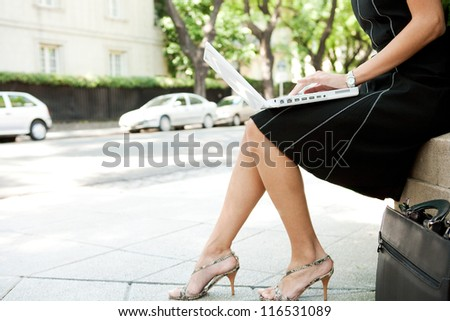 Low body section of a businesswoman using a laptop computer while sitting in a leafy classic city street. - stock photo