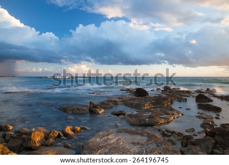 Low clouds above the stony shore of the sea. Seascape. - stock photo