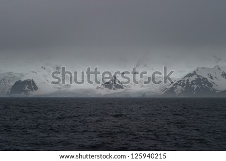 Low clouds cover the Southern Ocean and the Antarctic peninsula.  Weather in this area changes dramatically on a minute by minute basis. - stock photo