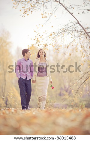 low contrast image of a happy young couple spending time outdoor in the autumn park - stock photo