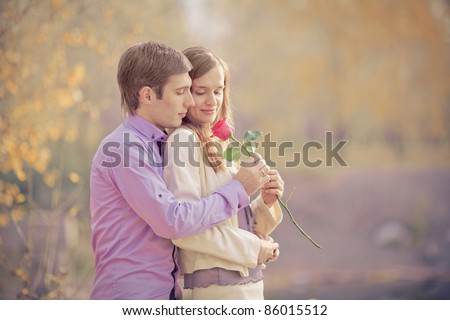 low contrast image of a happy young couple spending time outdoor in the autumn park (focus on the man) - stock photo