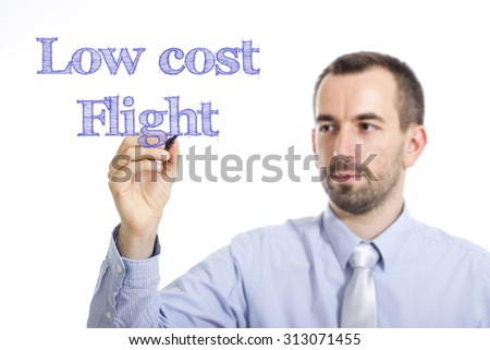 Low cost Flight - Young businessman writing blue text on transparent surface