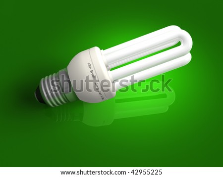 Low-energy lamp over green - stock photo