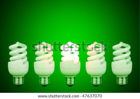Low energy lightbulb switched on in the centre of switched off light bulbs - stock photo