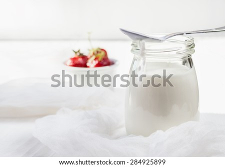 low-fat homemade yogurt with fresh strawberries on a light wooden background - stock photo