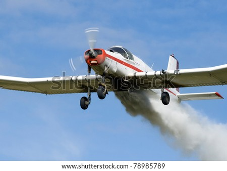 Low Flying Crop Duster Spraying Fertilizer - Close Up of Under Carriage - stock photo