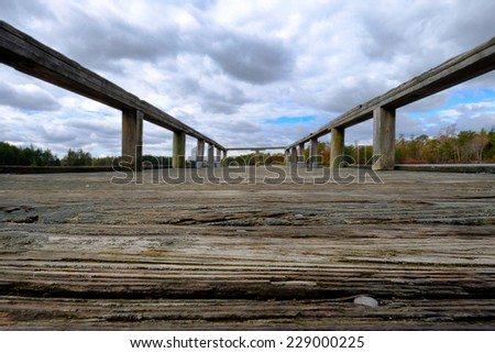 Low ground angle view of Rotting wood and nails  on a pier overlooking a lake - stock photo