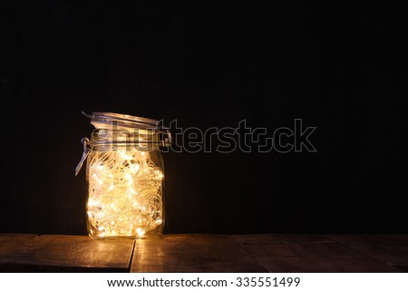 low key and vintage filtered image of fairy lights in mason jar with. selective focus  - stock photo