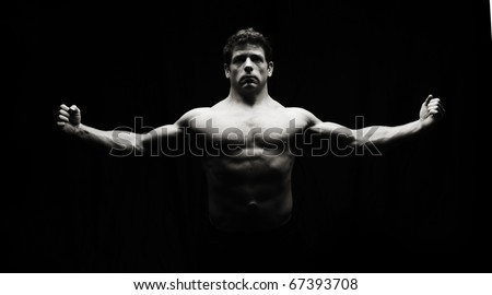 Low key artistic fitness man on black. Highlights muscular build of model.
