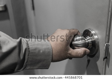 Low Key, close up business man hand opening the gray door. Business security concept. - stock photo