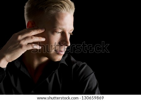 Low-key close up portrait of young attractive man in dark shirt with hand at temple looking aside, isolated on black background. - stock photo