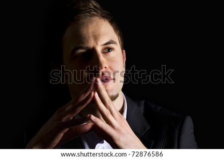 Low-key close up portrait of young smiling business executive in dark suit looking up and thinking, isolated on black background. - stock photo