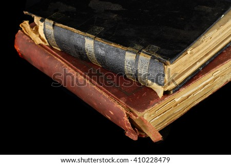 Low key closeup of very old books in poor condition on black background. There are two books. One has tape residue on the binding. The pages are yellowed with age. - stock photo