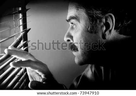 Low key concept photo of man looking furtively through window jalousies. Black&white grunge processed image with special grained texture added - stock photo