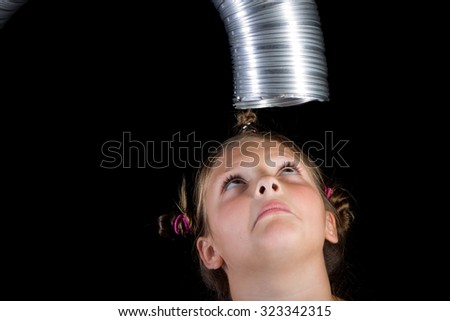 Low key concept shot of a kid looking up into a duct over her head making a mock fearful face