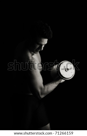 Low key fitness man lifting weights - stock photo
