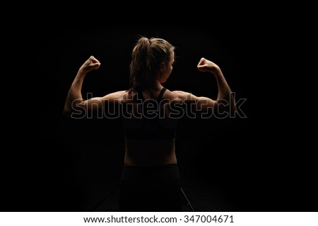 Low-key fitness model flexing - stock photo