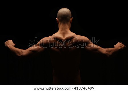 Low key fitness physique from back - stock photo