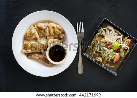 low key food background, grilled chicken spicy delicious papaya salad  on black tile - stock photo