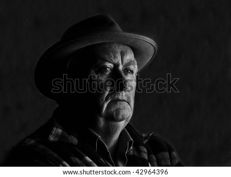 low key high contrast capture of a senior male with hat - stock photo