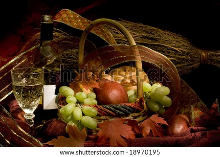 Low Key image of a basket of bread, pears and grapes with a bottle and glass of wine, ribbons and a cinnamon broom in the background. - stock photo