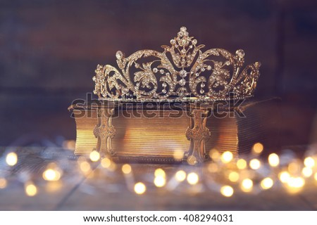 low key image of beautiful diamond queen crown on old book. vintage filtered with glitter overlay. selective focus. medieval period concept - stock photo