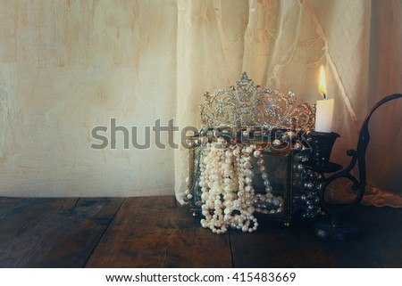 low key image of beautiful diamond queen crown, white pearls next to burning candle. vintage filtered and toned. fantasy medieval period