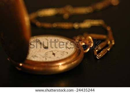 Low key image of broken antique pocket watch with chain.  Macro with extremely shallow dof.  Time concept.