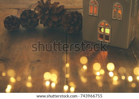 low key image of house lantern with burning candle and warm light in the windows over - Christmas Candle Lights For Windows