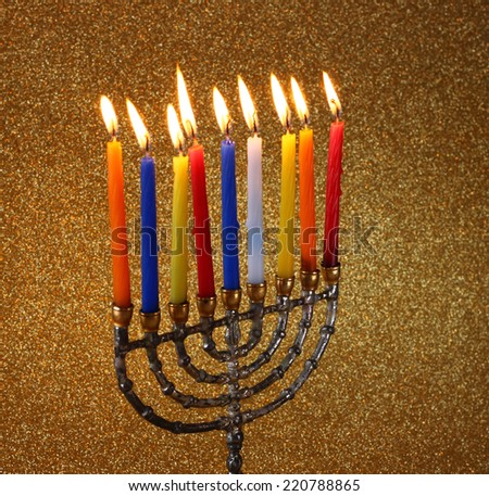 low key image of jewish holiday Hanukkah background with menorah Burning candles over golden dark glitter background  - stock photo