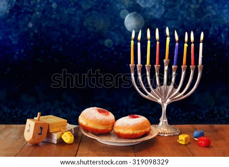 low key image of jewish holiday Hanukkah with menorah, doughnuts and wooden dreidels (spinning top). retro filtered image  - stock photo