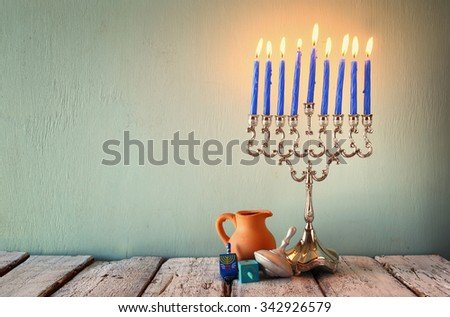 low key image of jewish holiday Hanukkah with menorah (traditional Candelabra) and wooden dreidels (spinning top).  retro filtered image  - stock photo