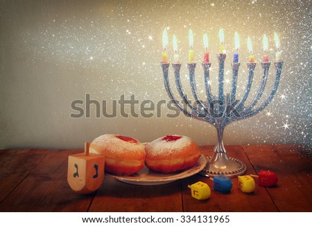 low key image of jewish holiday Hanukkah with menorah (traditional Candelabra), donuts and wooden dreidels (spinning top)  - stock photo
