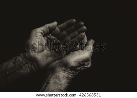 low key image of male Wrinkled old hands begging asking for money, help, reaching out and compassion concept. black and white photo  - stock photo