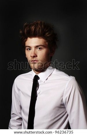 low key image of man in a shirt and tie looking at the camera - stock photo