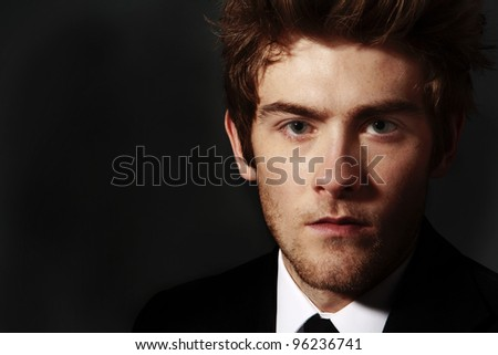 low key image of man in a shirt and tie looking at the camera