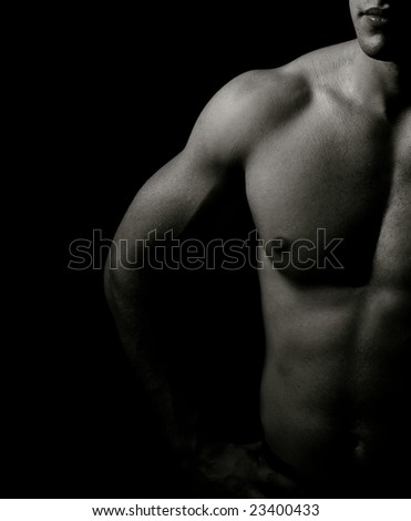 Low-key image of muscular masculine man - stock photo