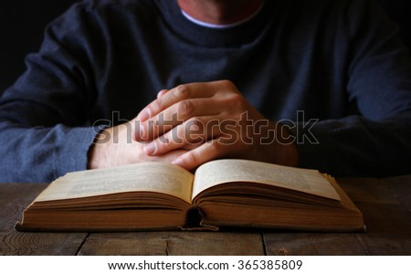 low key image of person sitting next to prayer book  - stock photo