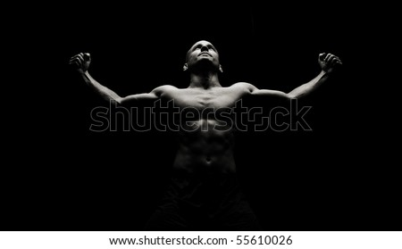 Low key image of strong male flexing - stock photo
