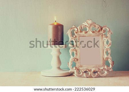 low key image of vintage antique classical frame and burning candle on wooden table